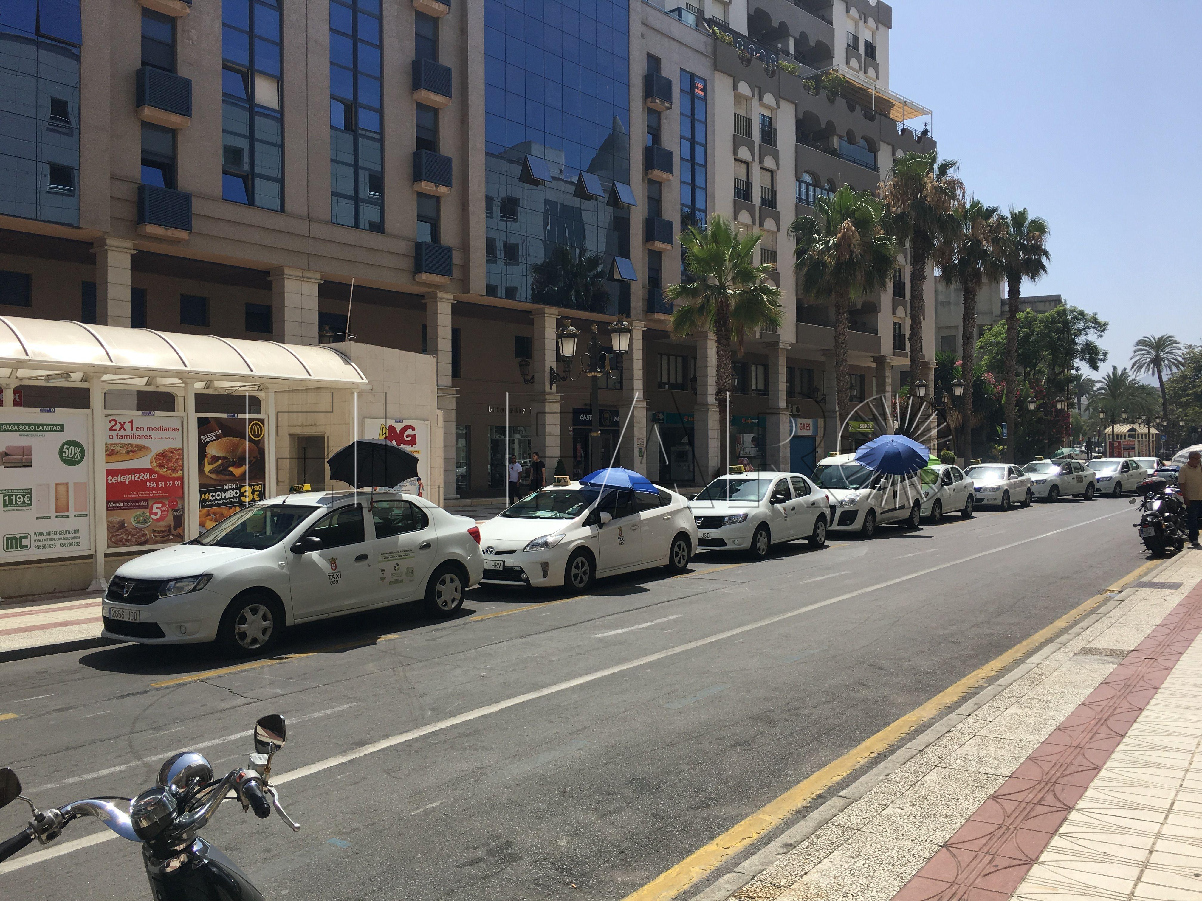 Los taxistas sacan sombrillas ante la falta de marquesinas prometidas